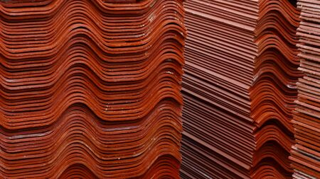 Stack red roof tiles, raw material for industrial of construction. Stock footage. Warehouse with red roof tiles Imagens - 128054274