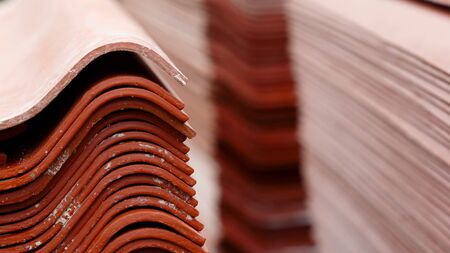 Stack red roof tiles, raw material for industrial of construction. Stock footage. Warehouse with red roof tiles