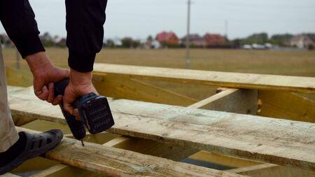 Man installing screw in wood board. Stock footage. Man screws a screw into the Board with a screwdriver 版權商用圖片