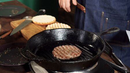 A hamburger patty frying on a cast iron grill. Stock footage. Hamburger Patty is prepared on the grill pan Imagens