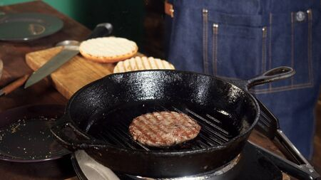 A hamburger patty frying on a cast iron grill. Stock footage. Hamburger Patty is prepared on the grill pan Imagens - 128054894