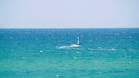Windsurfer riding the waves in the sea. Shot. Windsurfer in the sea, man on windsurf conquering the waves, enjoying extreme sport, active lifestyle, happy summer vacation Imagens - 128055173