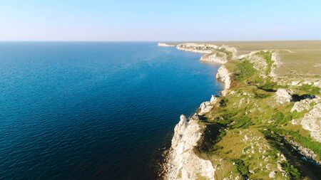 Aerial view of sea waves and fantastic Rocky coast. Shot. Top view of the rocky cliff by the sea Imagens - 128060161