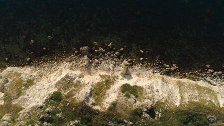 Aerial view of sea waves and fantastic Rocky coast. Shot. Top view of the rocky cliff by the sea