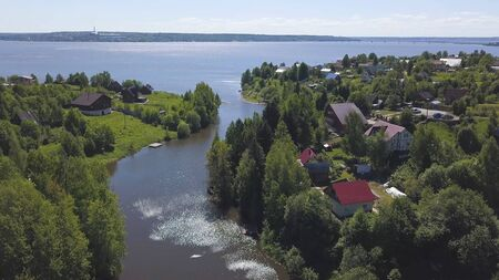 Breathtaking aerial view of the forested sea shore with small cottages in a summer sunny day. Small coastal village, beautiful houses near calm sea.