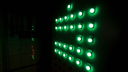 Primo piano del quadro elettrico con pulsanti e display luminoso in camera oscura. Pulsanti di controllo verdi sulla scheda.