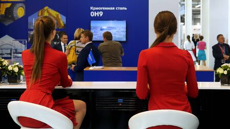 Rear view of two women in red jackets sitting at bar counter and putting notebooks on it at the exhibition. Girls in red suits and with ponytails working at the exhibition.