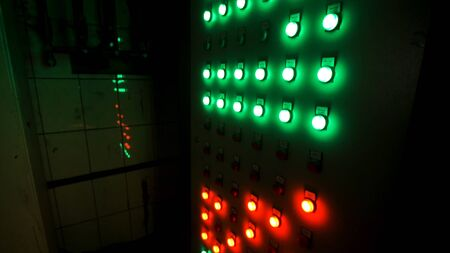 Many big red and green buttons on the industrial board at the factory. Industrial machines control panel push buttons in the dark room.