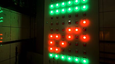 Many big red and green buttons on the industrial board at the factory. Industrial machine's control panel push buttons in the dark room.