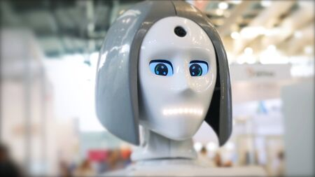 Close-up of moving and speaking female robots head with blue eyes. Different working robots collection presented on the robotics forum exhibition