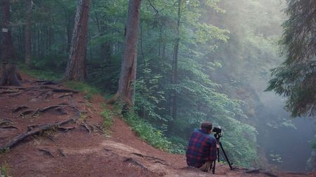 Man in plaid shirt and trousers sitting on the edge of deep ravine and taking a picture or video of landscape in a fog. Amazing view of mysterious forest Imagens - 127990058