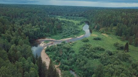 Aerial view of beautiful Russian river located between green meadow and mixed forest against cloudy sky in summer day. Picturesque view from above of Russian nature