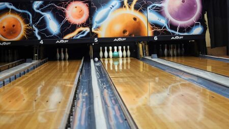 View of colorful ball hitting the bowling pins on bowling alley in a sport club. The bowling balls return machine system concept