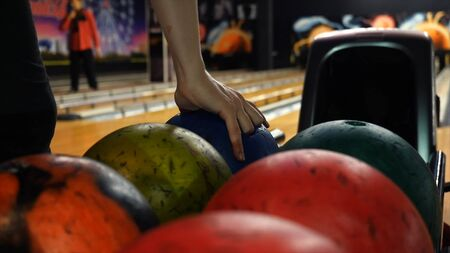 Close-up view of bowling player hand taking colorful ball from bowl lift. People playing bowling - the bowling balls return machine system concept