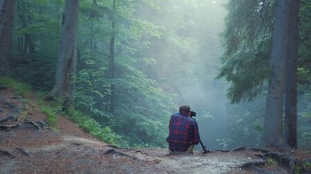 View of man in plaid shirt and trousers sitting on the edge of deep ravine and taking a picture or video of beautiful forest landscape in a fog. Amazing view of mysterious forest