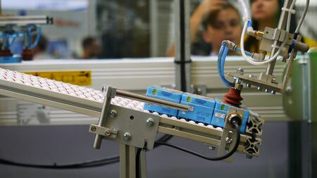 Close-up view of robotic machine sorting the juice boxing at the robotics forum exhibition and blurred figures of children on the background. Robots and innovative technologies in Russia