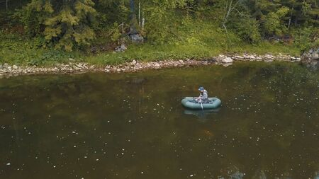 View of some man in camouflage coveralls fishing in green rubber boat on the river in summer day. Summer fishing season