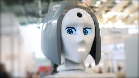 Close-up of moving and speaking female robot's head with blue eyes. Different working robots collection presented on the robotics forum exhibition Imagens - 127990161