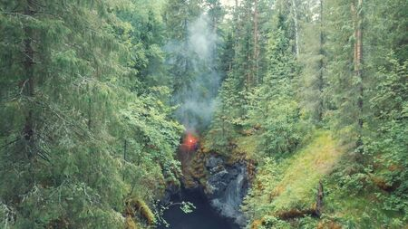 Aerial view of man standing on the edge of deep ravine with red signal flare in his hand in forest near the high old trees and shrubs. SOS signals in forest