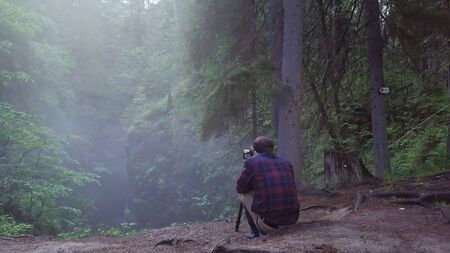Man in plaid shirt and trousers sitting on the edge of deep ravine and taking a picture or video of landscape in a fog. Amazing view of mysterious forest
