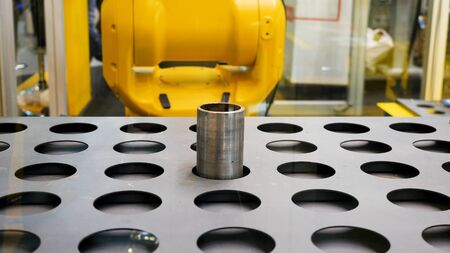 Close up for the robotic arm holding hollow metal tubes and putting them into the holes. Automated machine placing metal details into the holes of flat metal sheet.