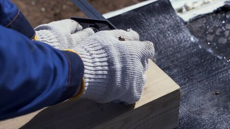 Close up for hands of a carpenter in protective gloves writing something on a wooden board. Joinery works, measuring and marking the wood, woodwork and furniture making concept.