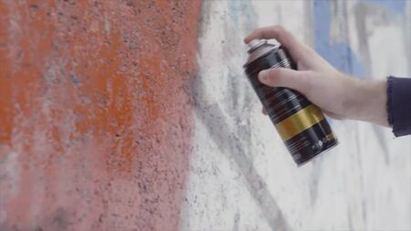 Hand holding a spray paint can and drawing colorful graffiti on the wall, street art concept. Side view of an artist painting with aerosol spray on the wall, concrete paint work.