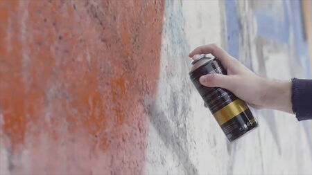 Close up of artist drawing and spraying paint on the wall, street art concept. Side view of a man hands during the process of creating graffiti on a concrete wall.