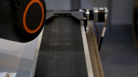 Movement of a metal detail on the black conveyor with a robotic hand hanging above it. Close up for the conveyor belt and the metal details on it.