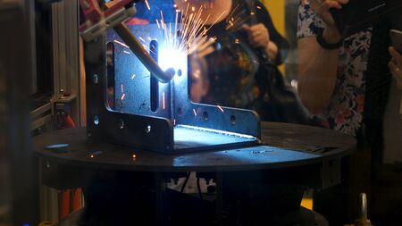 Robot welder at the exhibition, modern technologies concept. People looking at the automated welding process with many sparkles flying into the sides. Imagens