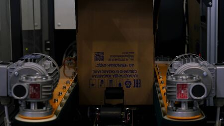 Close up for the automatic machine making cardboard boxes at the factory. Robotic mechanism wrapping card boxes, modern technologies.