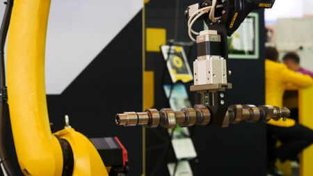 Industrial robotic machine putting down a metal detail, industrial international exhibition. Modern industrial technologies, robot holding metal detail. Imagens