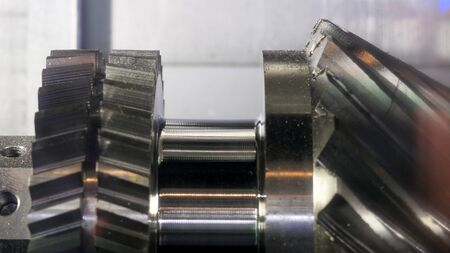 Close up for the rotating new metal gear at the factory, industrial concept. Media. Metal machine parts production.