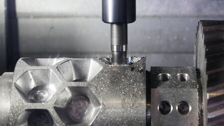 Close up for the automatic cutting machine carving holes in a metal detail at the plant. Media. Metal details production with metal shavings flying into the sides. Banque d'images - 128893554