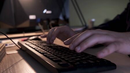 Close up of businessman hands typing on computer keyboard lying on a wooden table in the office, management concept. Stock footage. Male fingers typing message on the keyboard. Banque d'images - 128893545