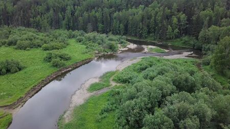 Top view of panorama of river passing through forest. Stock footage. Beautiful view of river reflecting sky and surrounding forest