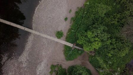 Top view of bridge passing through river in forest. Stock footage. Suspended wooden bridge passes through wide river in forest area Imagens