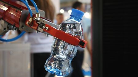 Large robotic hand holding and relocating a bottle with water with people on the background. Media. Different working robots collection presented on the robotics forum exhibition Banque d'images - 128893914