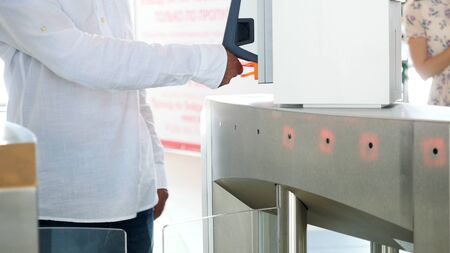 Man in white shirt and blue jeans passing electronic turnstile with barcode scanner. Media. Access control for business center, close-up Banque d'images - 128893923
