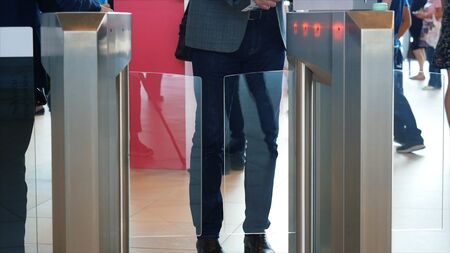 Man in grey suit jacket and blue jeans passing electronic turnstile with barcode scanner. Media. Access control for business center, close-up