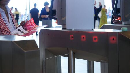 People of different ages passing electronic turnstile with barcode scanner. Media. Access control for business center, close-up Banque d'images - 128894954