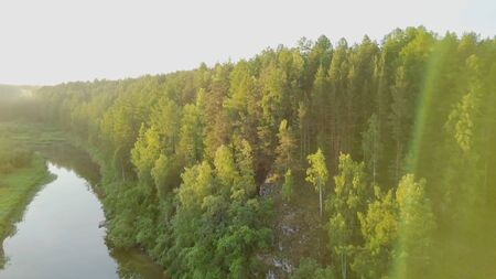 Bright sunny rays falling on green forest by river. Stock footage. Warm sunlight falls on beautiful dense forest with river reflecting clear sky. Summer sunny landscape with forest Banque d'images - 128895292
