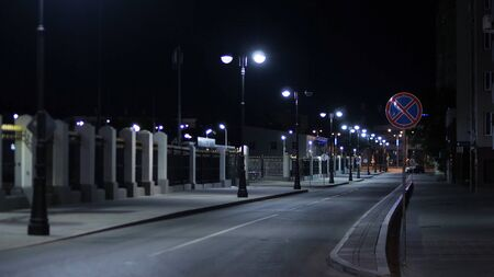 Empty roadway lit by lanterns on night. Stock footage. Summer night in city illuminated by white lights empties on roads at later time Banque d'images - 128898926