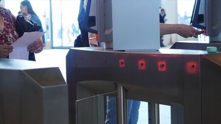 People of different ages passing electronic turnstile with barcode scanner. Media. Access control for business center, close-up Banque d'images - 128898908