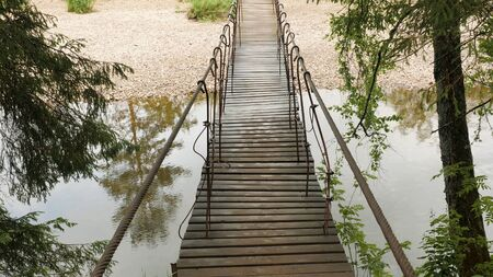 Wooden bridge suspended over forest river. Stock footage. Old hanging wooden bridge over which travelers are afraid to cross Banque d'images - 128898925