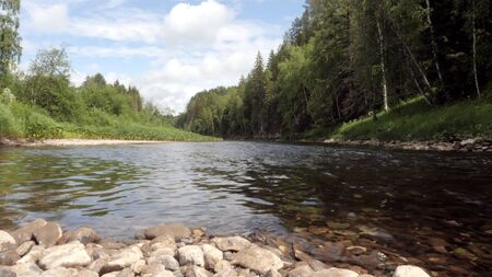 Mountain river flowing on background of green forest. Stock footage. Streams of mountain river calms and fills with force. Cold mountain river in forest invigorate hiking in hot summer Banque d'images - 128898937