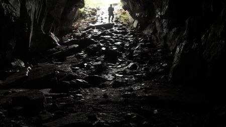 Le voyageur descend dans la grotte. Images d'archives. Le voyageur explore le tunnel de la grotte en descendant la corde. Tunnels de grottes dangereux, glissants de l'humidité et inspirant la peur de l'obscurité inconnue
