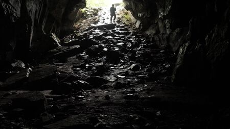 Traveler descends into cave. Stock footage. Traveler explores cave tunnel going down rope. Dangerous cave tunnels, slippery from damp and inspire fear of unknown darkness