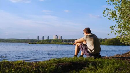 Young man sits on shore of river on background of city. Stock footage. Man enjoys views of nature sitting by river. Nature, waves on river and on background you can see high-rises of city