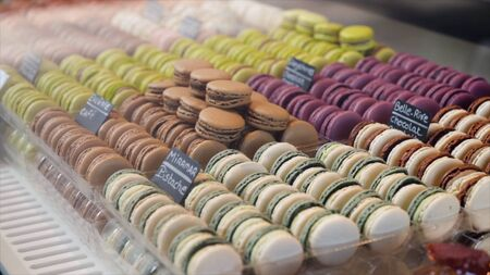 Close-up of variety of macaroon cookies. Action. Macaroon almond cookies win hearts of many sweet lovers. Macaroons for every taste and color in French bakery